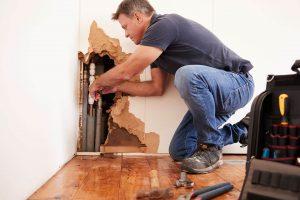 middle-aged-man-repairing-burst-water-pipe