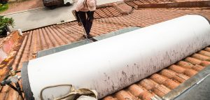 worker-fixing-solar-water-heater-on-roof