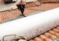 worker fixing solar water heater on roof